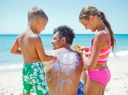 父の背中に日焼け止めクリームを適用する熱帯のビーチで彼の妹と愛らしい少年 写真素材