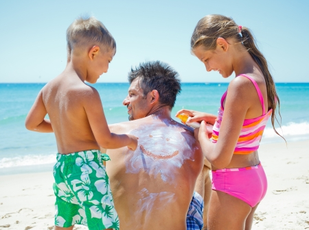 Adorable boy with his sister at tropical beach applying sunblock cream on a father s back