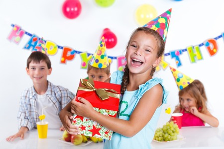 Beautiful girl with giftbox looking at camera having fun at birthday party with his friends on background