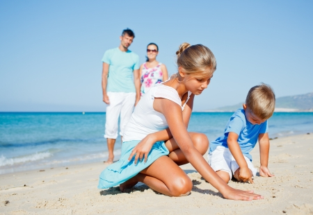 Family of four having fun on tropical beach - two cute kids playing with sand photo