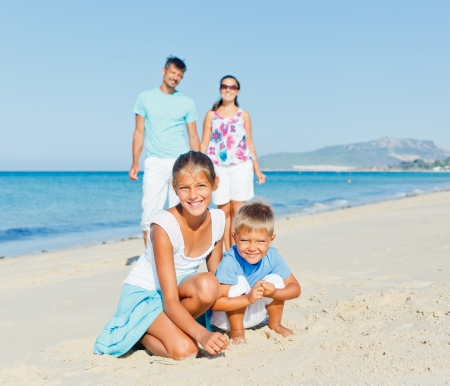 Two cute kids playing on tropical beach with their parents photo