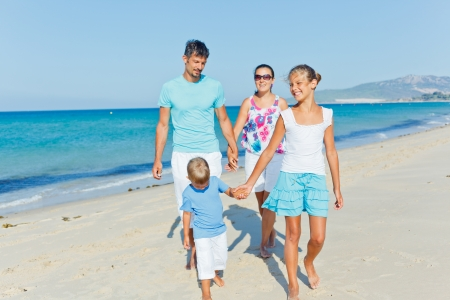 Family of four having fun on tropical beach photo