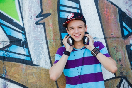 Close-up portrait of happy teens boy with headphones near painted wall listening to music