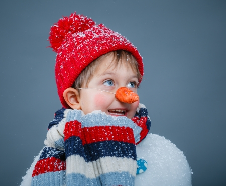 Portrite of cute little boy in suit snowman in red hat and mittens