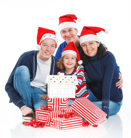 Christmas theme - Portrait of friendly family in Santa s hat with gift box, isolated on white photo