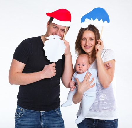 Christmas theme - Portrait of happy family with baby in Santa s hat, isolated on white  photo
