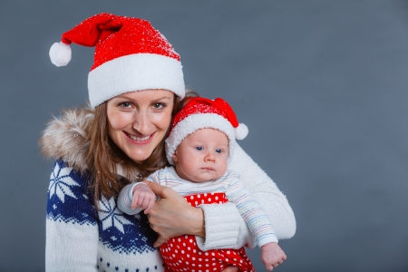 babyboy: Christmas theme - Portrait of happy mother with babyboy in Santa s hat in studio