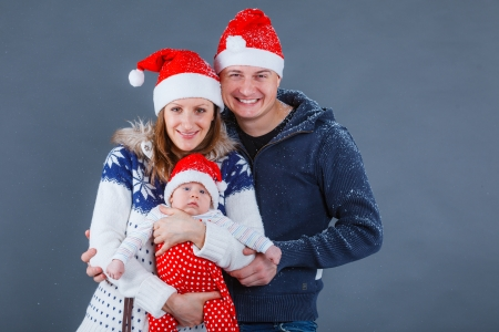 Christmas theme - Portrait of happy family with baby in Santa s hat in studio photo