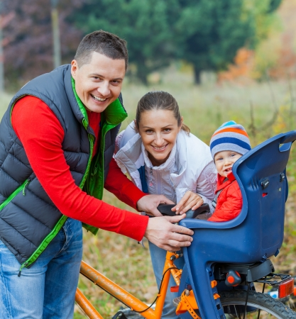 Family with baby on bikes in the autumn park