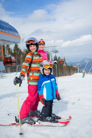 Two happy smiling kids in ski goggles and a helmet with his mother in the mountains photo