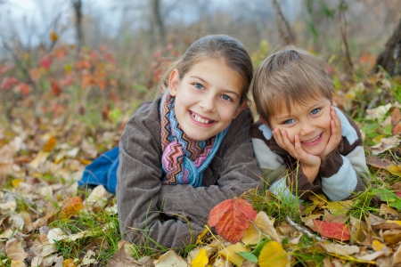 Happy kids lying on autumnal ground covered with dry leaves photo