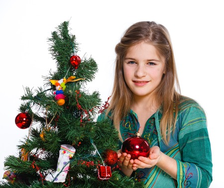 Christmas theme - Beautiful girl decorating christmas tree  Isolated on white backround  photo