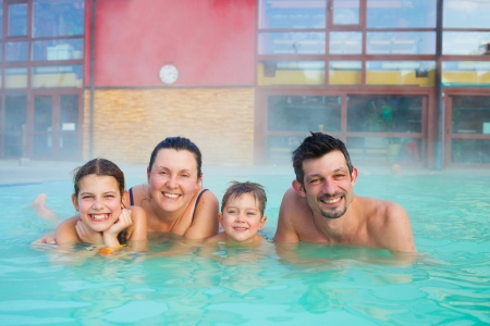 Activities on the pool  Portrait of happy family of four relaxing in termal swimming pool photo