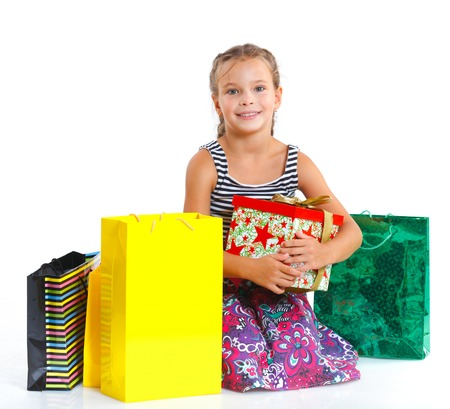 Shopping little girl happy smiling holding shopping bags isolated on white photo