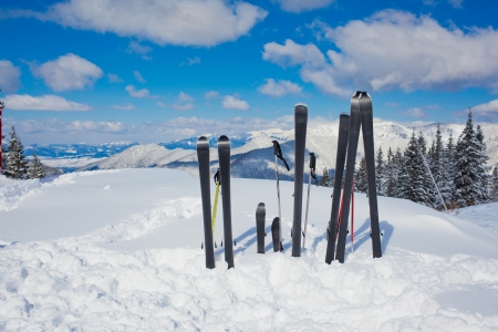 A family set of skis, ski poles in the snow mountains  photo