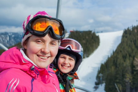 Portrait of happy woman in ski goggles and a helmet with daughter on the ski lift photo