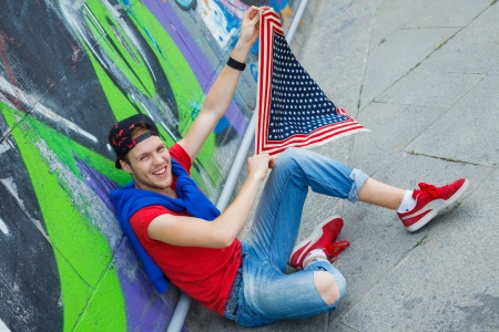 18 20: Happy teens boy sitting near painted wall and having fun with american flag Stock Photo