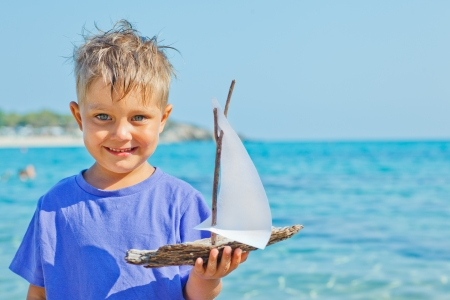 Cute boy with toy ship in hands ashore  Vertical view photo