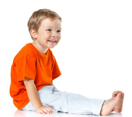 preadolescence: Adorable happy boy sitting on the floor in studio  Isolated of white background