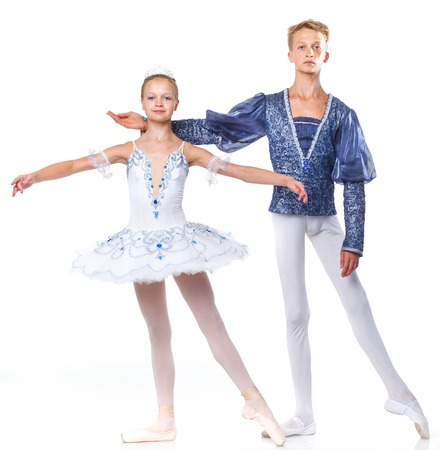Couple of young ballet dancers posing over isolated white background photo
