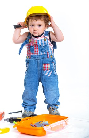 Little builder  Baby boy in a helmet plays in the builder with tools  Isolated over white Stock Photo - 23956850