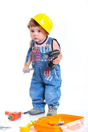 ヘルメットの男の子ビルダーを白で分離されたツールとビルダーで果たしています。 写真素材