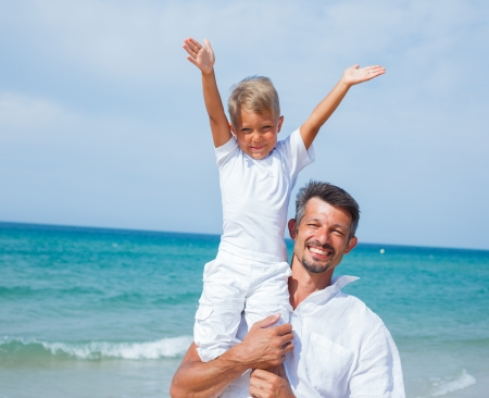 Father and son having fun on tropical beach photo