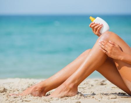 Las piernas de la chica joven de aplicar bloqueador solar al estar sentado en una playa en verano
