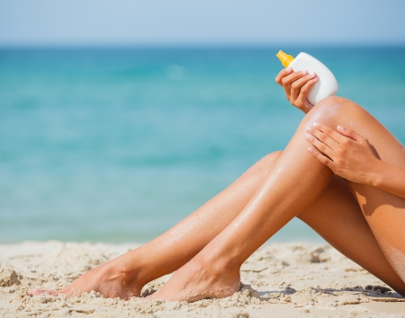 sunblock: Legs of young girl applying sunblock while sitting on a beach in summer  Stock Photo