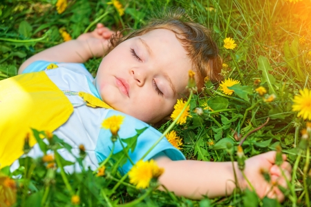 Closeup portrait of a little baby boy sleeping outdoors on grass  photo