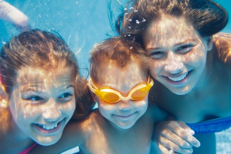 Close-up underwater portrait of the three cute smiling kids photo