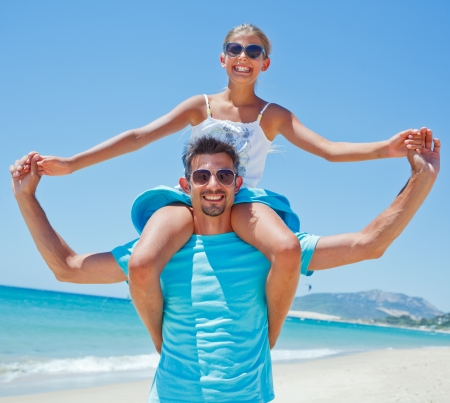 Father and daughter having fun on tropical beach photo