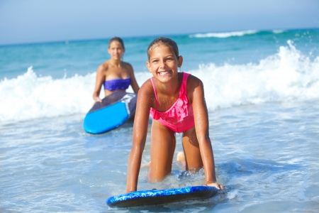 fun day: Summer vacation - Two cute girls having fun with surfboard in the ocean Stock Photo