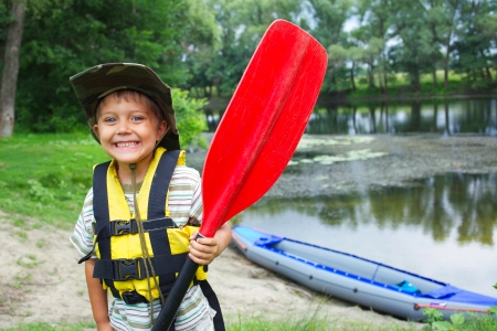 canoes: Portrait of happy young boy holding paddle near a kayak on the river, enjoying a lovely summer day Stock Photo