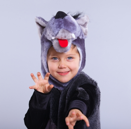 A portrait of a little boy trying a carnival suit of wolf on the grey  photo