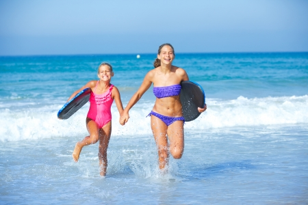 Summer vacation - Two cute girls in bikini with surfboard running from the ocean  photo