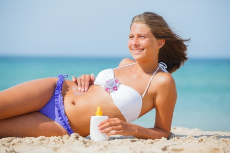 Beautiful young girl applying sunblock on a beach in summer  photo