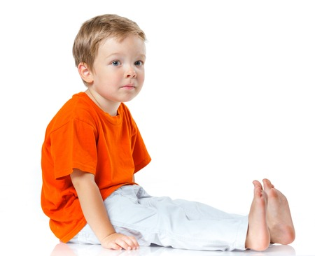 Adorable happy boy sitting on the floor in studio  Isolated of white  photo