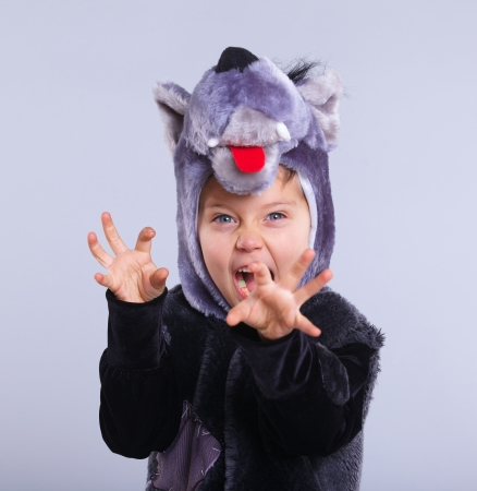 A portrait of a little boy trying a carnival suit of wolf on the grey background Standard-Bild