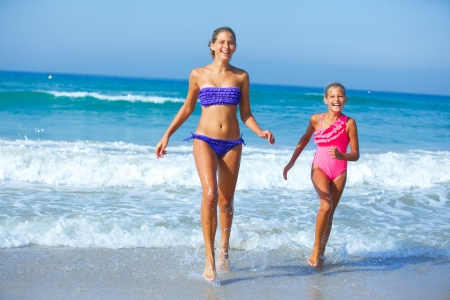 Cute girls friends running together in the beach shore on summer vacation photo