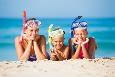 Three happy children on beach with colorful face masks and snorkels