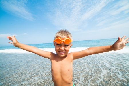 Playful boy in swimming goggles on the beach photo