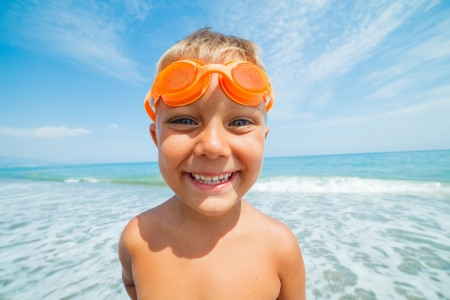 Playful boy in swimming goggles on the beach