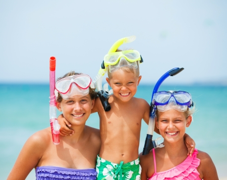 Closeup portrait of three happy children on beach with colorful face masks and snorkels photo