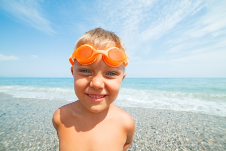 swimming goggles: Playful boy in swimming goggles on the beach