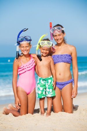 Three happy children on beach with colorful face masks and snorkels photo