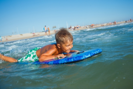 Boy has fun on the surfboard in transparency sea Stock Photo - 24727295