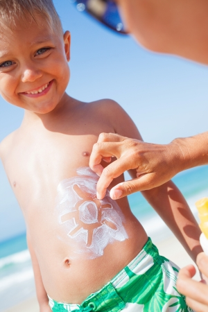 Adorable boy and mother at tropical beach applying sunblock cream