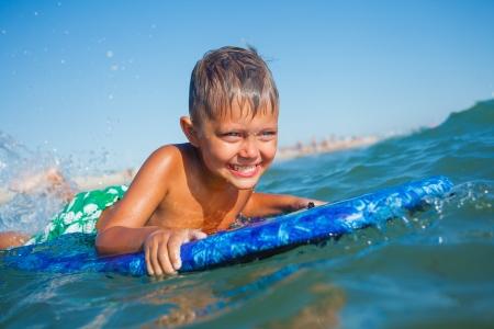 bodyboarder: Boy has fun on the surfboard in transparency sea Stock Photo
