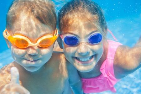 natacion: Close-up retrato bajo el agua de los dos ni�os sonrientes lindos